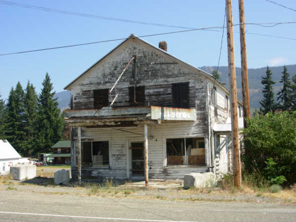 front view of an old battered but still stannding 2-story wood structure.