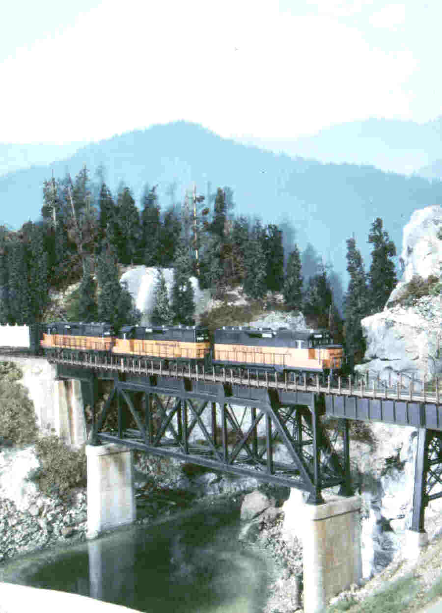 Steve Depolo's Milwaukee Road - layout. Photo of a bridge, a tall steel trestle crossing a gorge, atop concrete piers and abutments by C. C. Crow. This C. C. Crow photo appeared on cover of Mainline Modeler magazine.